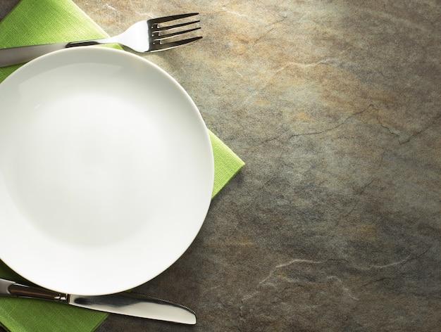 Prato, faca e garfo no fundo da mesa