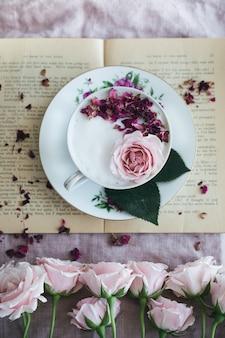 Prato floral branco e rosa redondo com uma xícara de chá e rosas