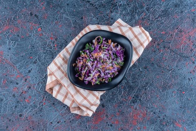 Prato fundo preto com salada de legumes em uma toalha de mesa