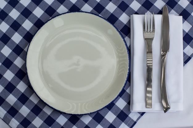 Prato, garfo e faca sobre uma mesa servida com toalha de mesa quadriculada branca azul. conceito de restauração.