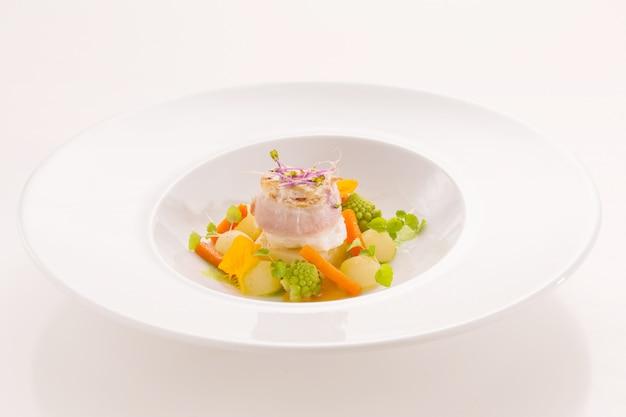 Prato gourmet com peixe e legumes pequenos