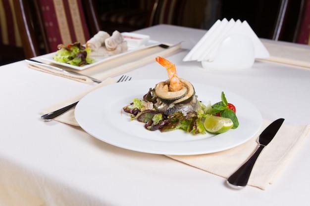 Prato gourmet de frutos do mar com carne de peixe e camarão com legumes com limão. preparado em placa redonda branca. servido à mesa do restaurante.