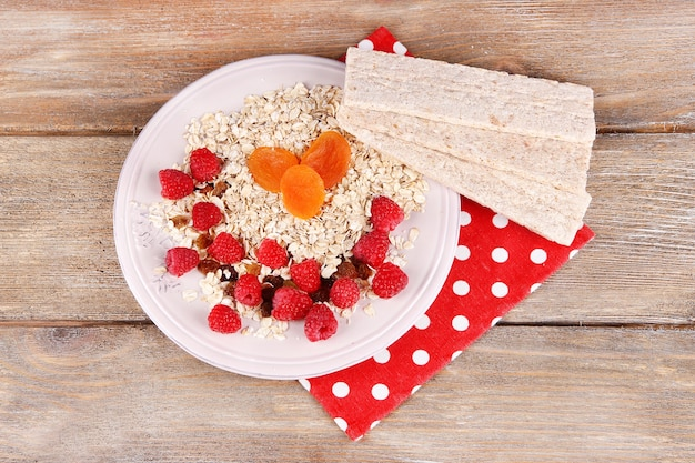 Prato grande com mingau de aveia, pequenos pães e frutas em um guardanapo de bolinhas no fundo de madeira