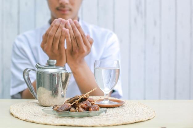 Prato iftar com mão de homem muçulmano orando a alá
