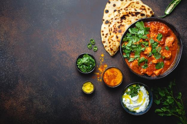 Prato indiano autêntico frango tikka masala com espaço para texto. carne picante de curry em uma tigela com pão fresco naan, molho raita de iogurte em fundo escuro rústico, vista de cima, close-up, espaço de cópia