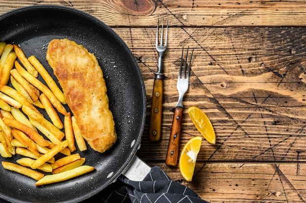 Prato inglês tradicional de peixe com batatas fritas em uma panela