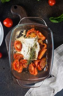 Prato italiano de massa misturada com queijo feta assado e tomate em um fundo escuro. fetapasta. receita viral em alta, flat lay, cópia espaço