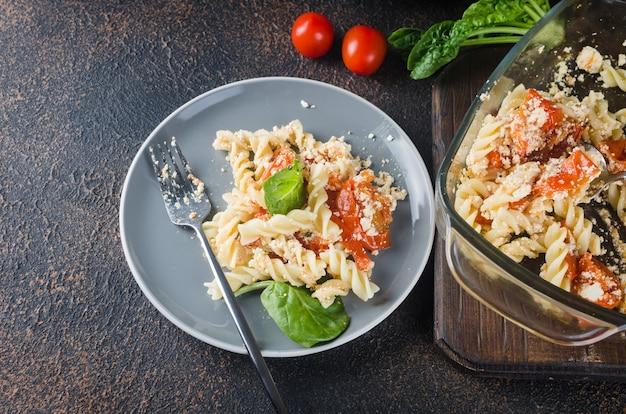 Prato italiano de massa misturada com queijo feta assado e tomate em um fundo escuro. fetapasta.
