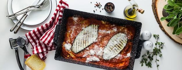 Prato italiano de melanzane alla parmigiana, feito de berinjela e tomate em uma mesa