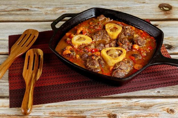 Prato italiano de ossobuco com pernil, pimentão, cebola e vinho.
