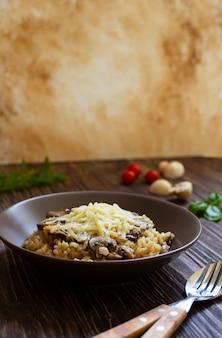 Prato italiano tradicional de risoto de arborio de arroz com cogumelos. servido com manjericão fresco, cogumelos e tomate cereja em uma mesa de madeira escura. vertical. fechar-se. fundo de mármore claro