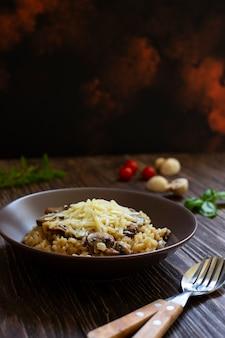 Prato italiano tradicional de risoto de arborio de arroz com cogumelos. servido com manjericão fresco, cogumelos e tomate cereja em uma mesa de madeira escura. vertical. fechar-se. fundo de mármore escuro