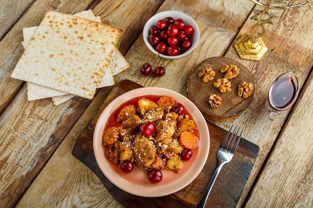 Prato judeu guisado de batata com frango ao molho cereja, decorado com cerejas em uma barraca ao lado de matzá e menorah.