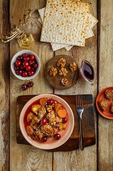 Prato judeu guisado de batata com frango ao molho cereja decorado com cerejas na mesa em um prato ao lado de pão ázimo e menorá. foto vertical