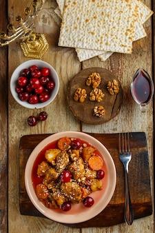 Prato judeu guisado de batata com frango ao molho cereja decorado com cerejas na mesa em um prato ao lado de pão ázimo e menorá.