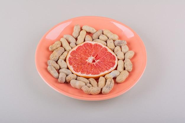 Prato laranja com fatia de toranja e amendoim orgânico em fundo branco. foto de alta qualidade