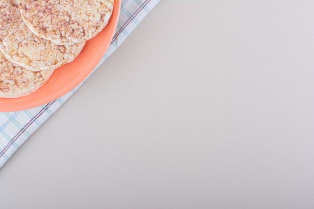 Prato laranja de deliciosos bolos de arroz na mesa branca. foto de alta qualidade