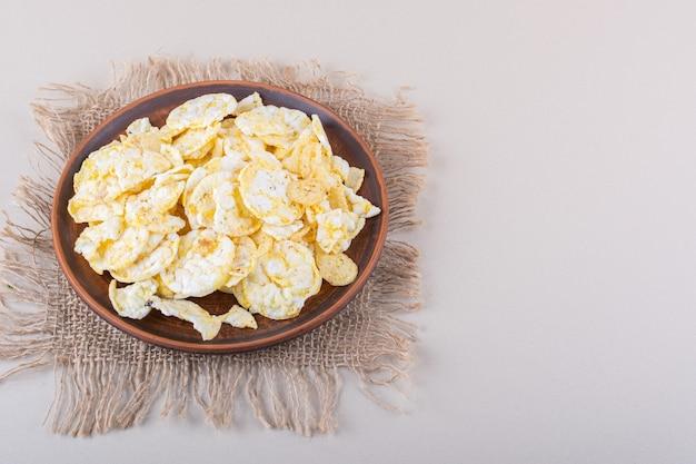Prato marrom de chips de arroz crocante na mesa branca