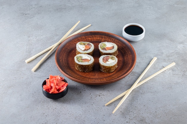 Prato marrom de saboroso sushi rola com gengibre em conserva e soja na pedra.