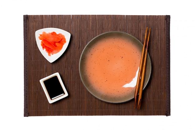 Prato marrom redondo vazio com pauzinhos para molho de sushi, gengibre e soja no fundo de esteira de bambu escuro