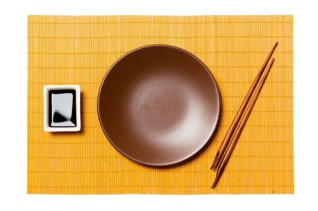 Prato marrom redondo vazio com pauzinhos para sushi e molho de soja na esteira de bambu amarelo