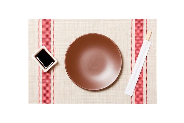 Prato marrom redondo vazio com pauzinhos para sushi e molho de soja no fundo da esteira de sushi. vista superior com espaço de cópia para você projetar.