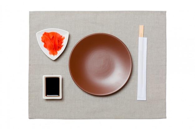 Prato marrom redondo vazio com pauzinhos para sushi, gengibre e molho de soja, guardanapo cinza