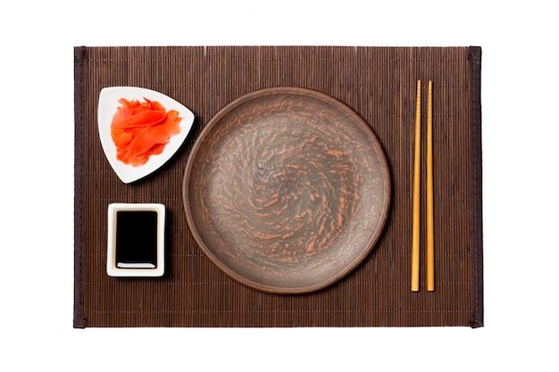 Prato marrom redondo vazio com pauzinhos para sushi, gengibre e molho de soja na esteira de bambu escuro