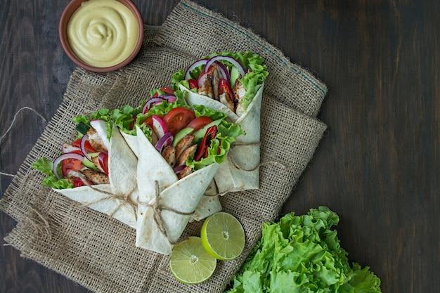 Prato mexicano. burrito embrulhado com frango e legumes close-up