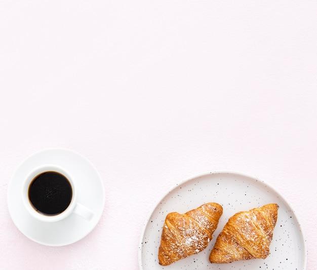 Prato minimalista com croissants franceses e café