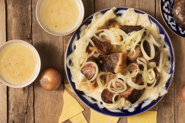 Prato nacional do cazaque - beshbarmak e caldo nas taças