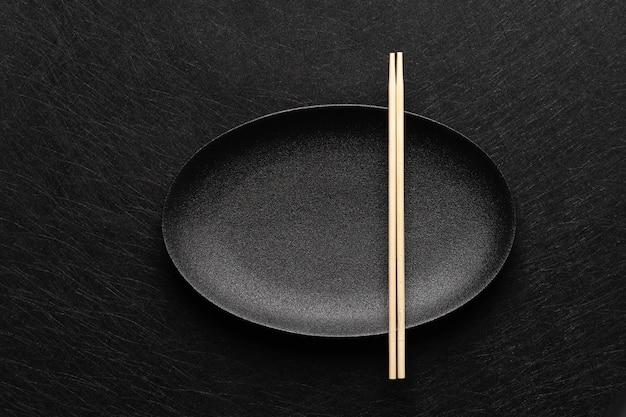 Prato oval preto vazio com pauzinhos na mesa escura. estilo de comida japonesa. vista do topo