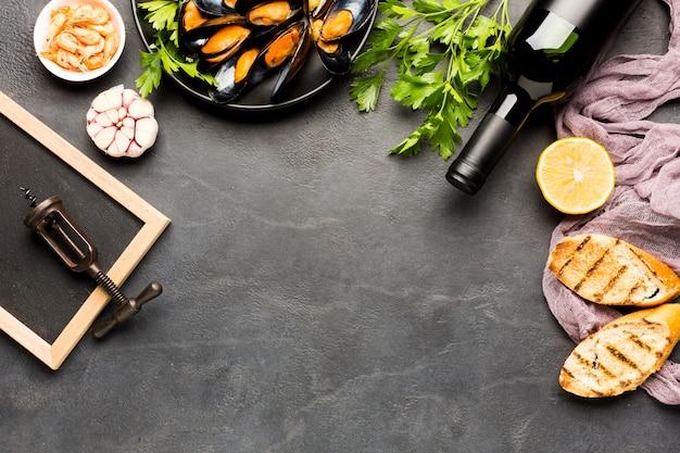 Prato plano de mexilhões cozidos e vinho com copyspace