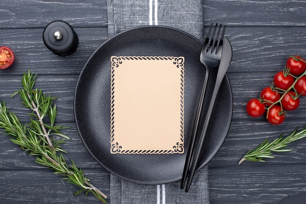 Prato plano leigo com talheres e tomate
