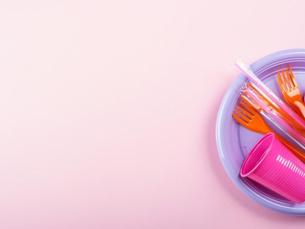 Prato plástico colorido descartável, palha e vidro