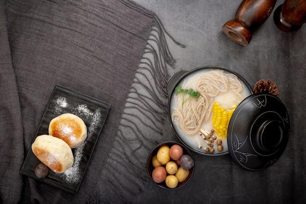 Prato preto com panquecas e uma tigela com macarrão