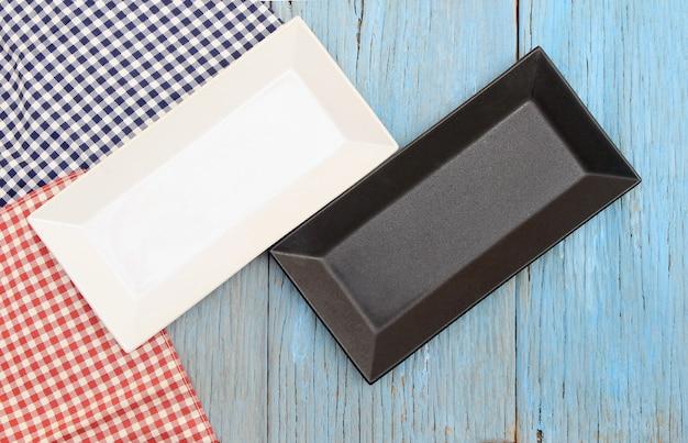 Prato preto e branco na toalha de mesa no fundo da mesa de madeira