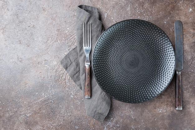 Prato preto vazio com guardanapo, garfo e faca sobre pedra escura
