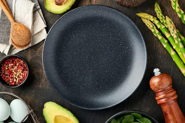 Prato preto vazio e bando de espinafre de aspargos orgânicos verdes frescos, abacate, ovos de galinha, tempero de pimenta em fundo de madeira velho. configuração da tabela. fundo de cozimento de alimentos, espaço de cópia.