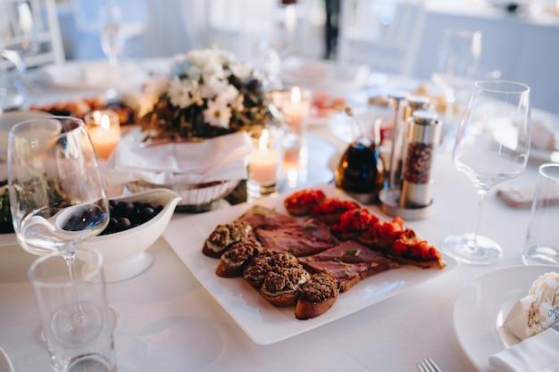 Prato quadrado branco com fatias de bruschetta e azeitonas pretas em uma tigela sobre uma mesa decorada com um