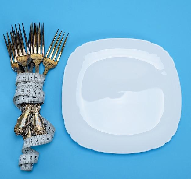 Prato quadrado branco vazio e garfos envolto em uma fita métrica