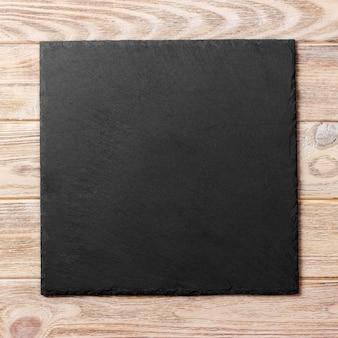 Prato quadrado na mesa. prato preto em madeira. copie o espaço