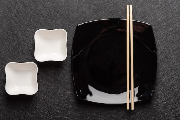 Prato quadrado preto vazio com pauzinhos e duas molheiras brancas em um fundo escuro japonês