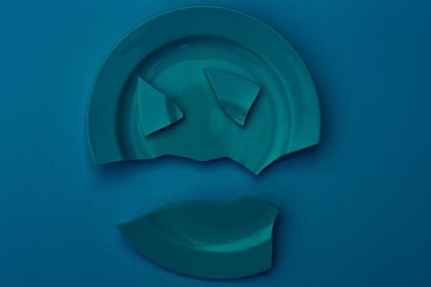 Prato quebrado azul sobre um fundo azul. conceito de relacionamento familiar, divórcio, horror.