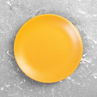 Prato redondo amarelo na mesa de cimento cinza