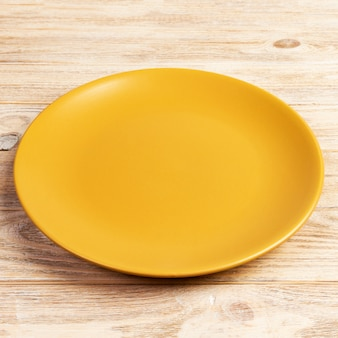 Prato redondo amarelo na mesa de madeira