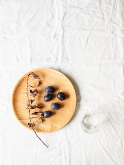 Prato redondo caseiro de madeira com ameixas e galho seco