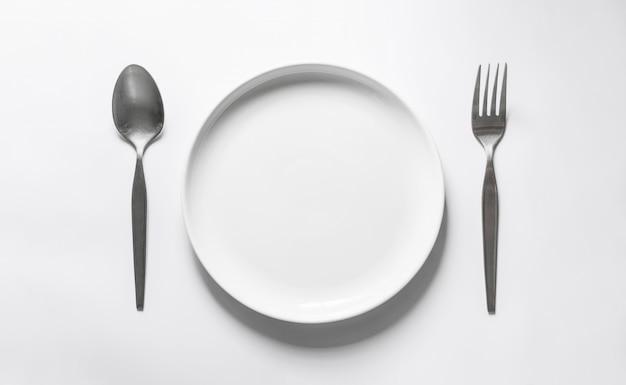 Prato redondo cerâmico com prateado garfo e colher, na mesa branca