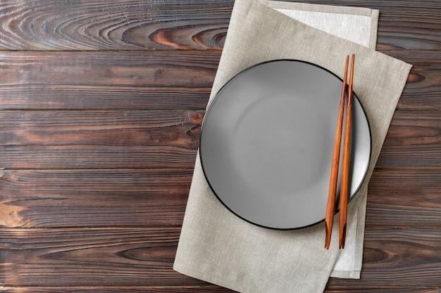 Prato redondo cinzento vazio com pauzinhos para sushi na madeira