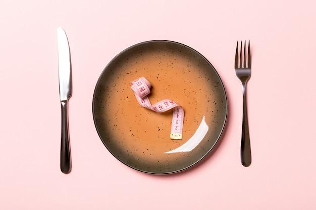 Prato redondo com fita métrica dentro com garfo e faca em fundo rosa. vista superior da obesidade